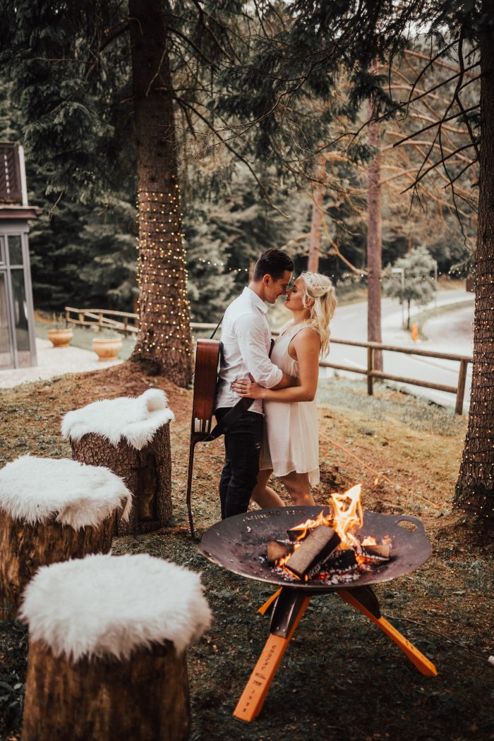 Couple in the woods next to a fire