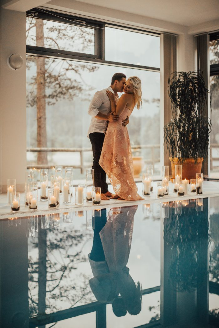 Couple next to a romantic pool lit by candle light
