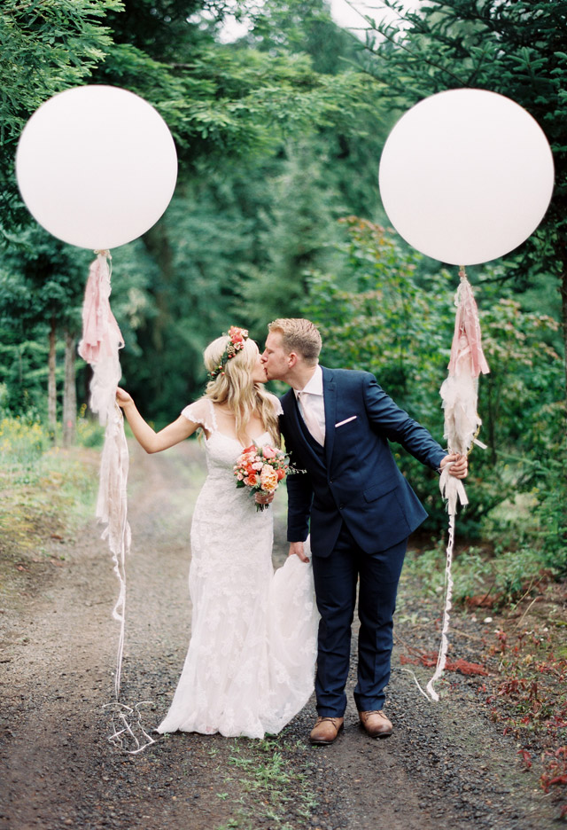 Bride wearing Alexa with Groom in the woods holding pink balloons