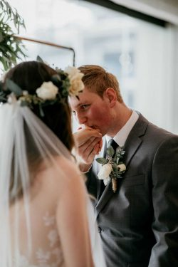 Groom Kissing Real Bride Wearing Flower Crown and Camille Wedding Gown by Rebecca Ingram