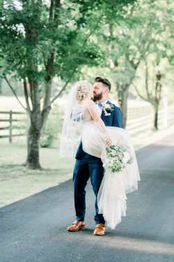 Groom Holding Bride Wearing Olson Wedding Dress by Sottero and Midgley