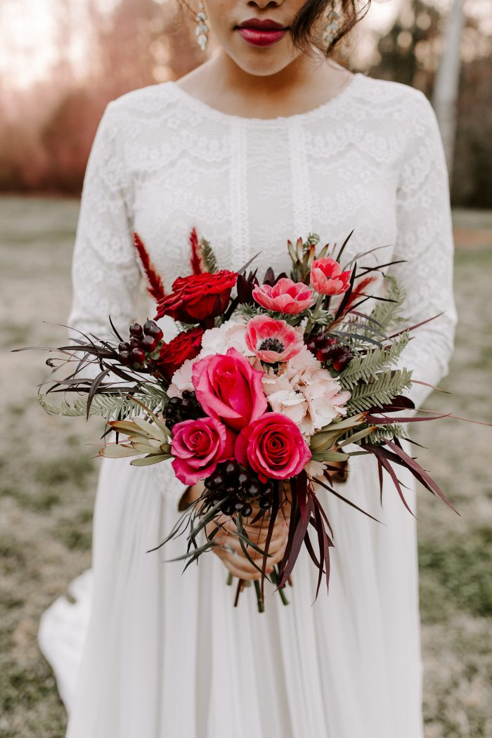 Real Bride Wearing Modest Lace Wedding Dress Called Deirdre Marie by Maggie Sottero and Holding Red and Pink Bouquet