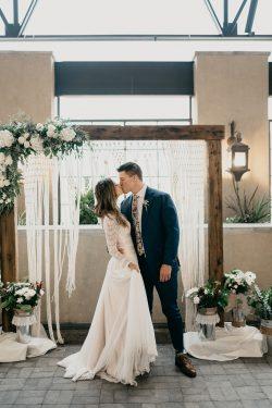 Groom Kissing Bride Wearing Boho Wedding Dress Called Deirdre by Maggie Sottero