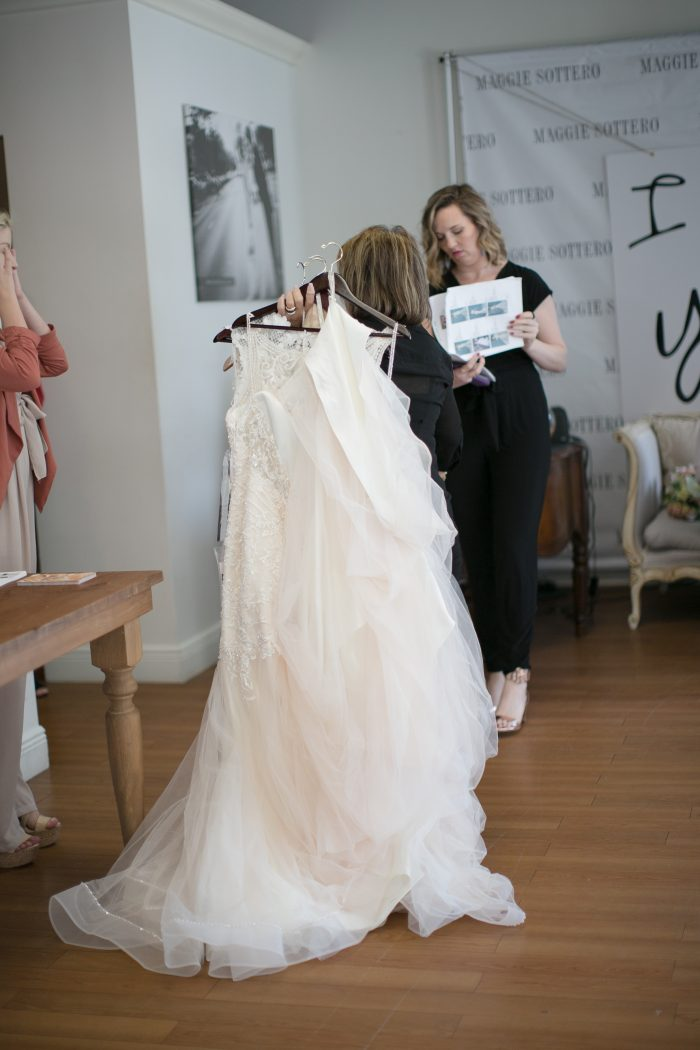 Stylist Holding Selections of Wedding Dresses for Brides to Try On