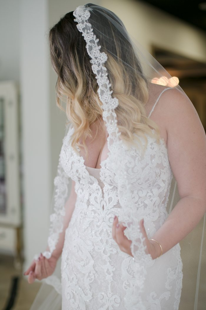 Bride Trying on Maggie Sottero Wedding Dress at a Store Event