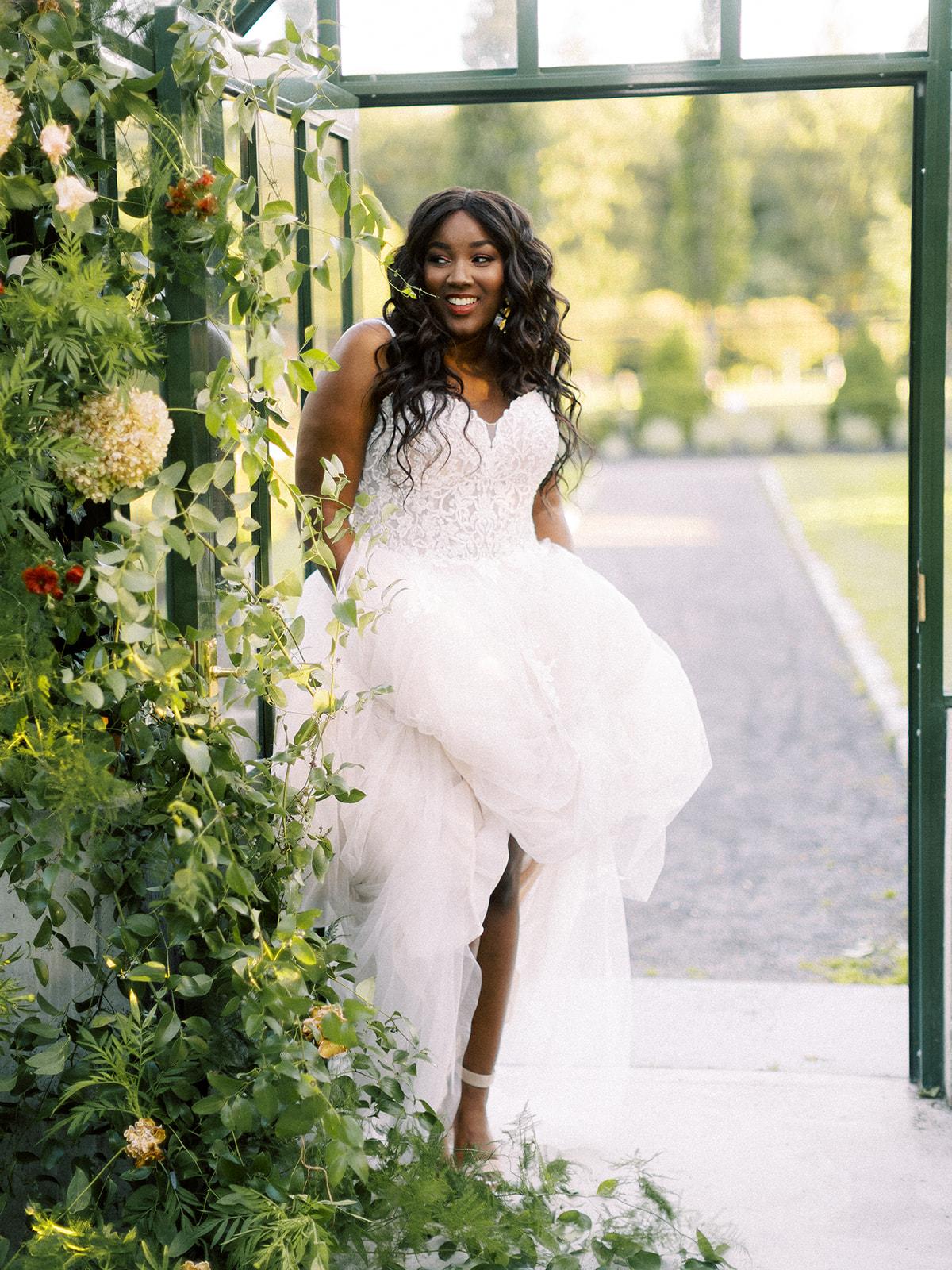 Model in Greenhouse Wearing Plus Size Lightweight A-line Wedding Dress Called Marisol by Rebecca Ingram
