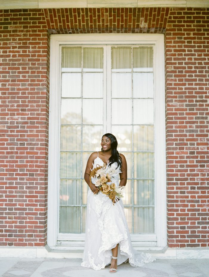 Bride Wearing Lace Boho Sheath Wedding Dress Called Tuscany Lane by Maggie Sottero in front of brick building
