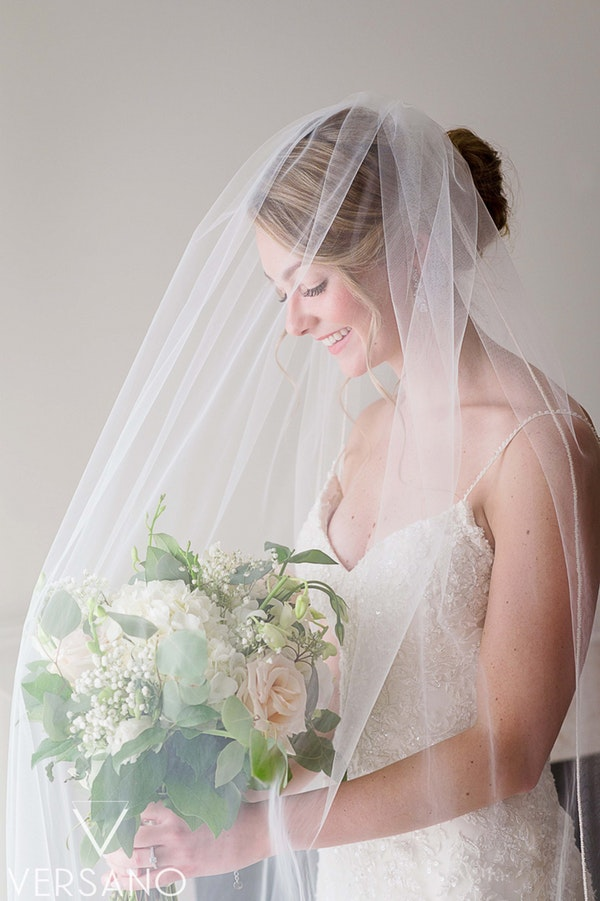 Real Bride Wearing Sheath Wedding Dress Called Nola by Sottero and Midgley and holding White Bouquet