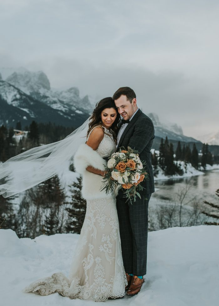 Groom Hugging Bride at Winter Wedding and Bride Wearing Winifred Wedding Dress by Maggie Sottero
