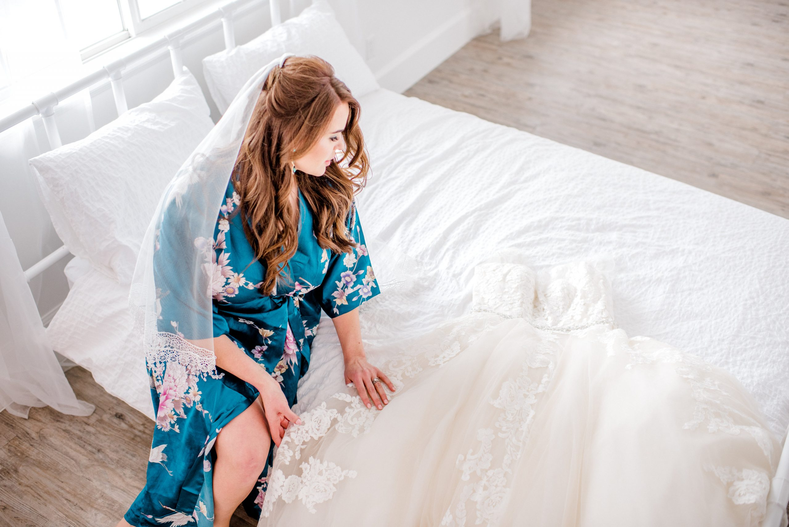 Bride in Robe on a Bed Looking at her Wedding Dress by Maggie Sottero Cover Photo