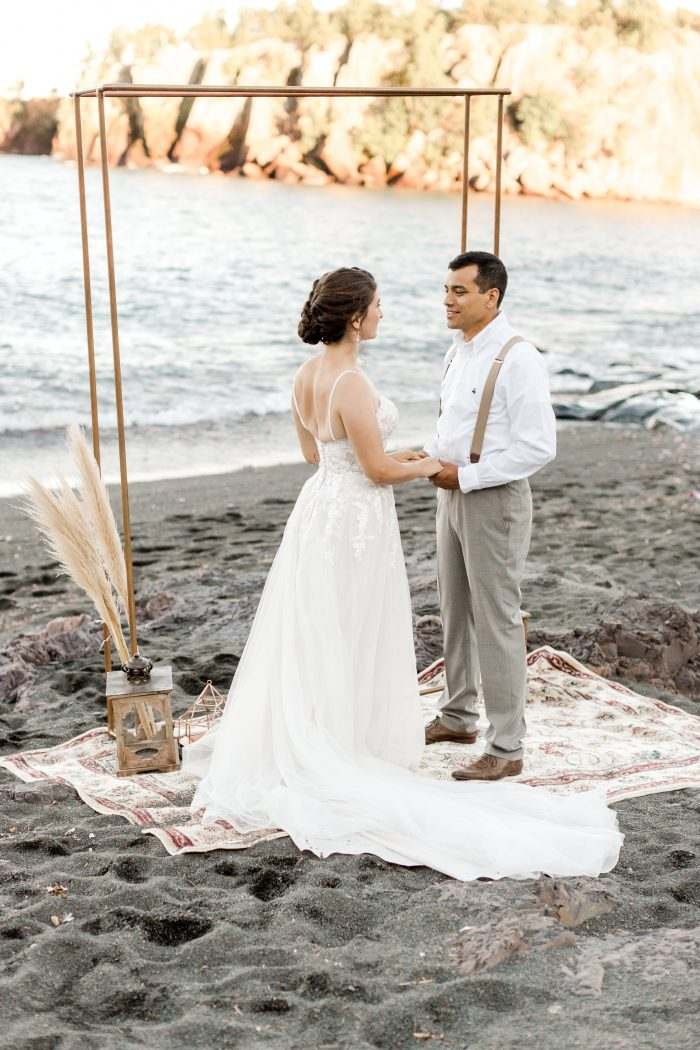 Bride and Groom Saying Wedding Vows in Front of Wedding Arch on Black Sand Beach
