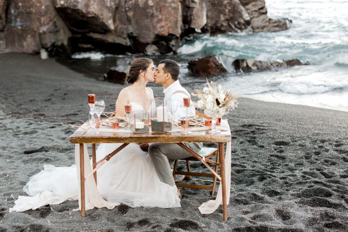 Real Bride and Groom sitting at Reception Table at Intimate Beach Wedding on a Black Sand Beach