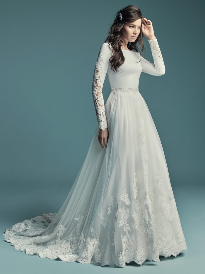 Model Wearing Long Sleeve Sheath Wedding Gown with Detachable Overskirt Called Olyssia by Maggie Sottero