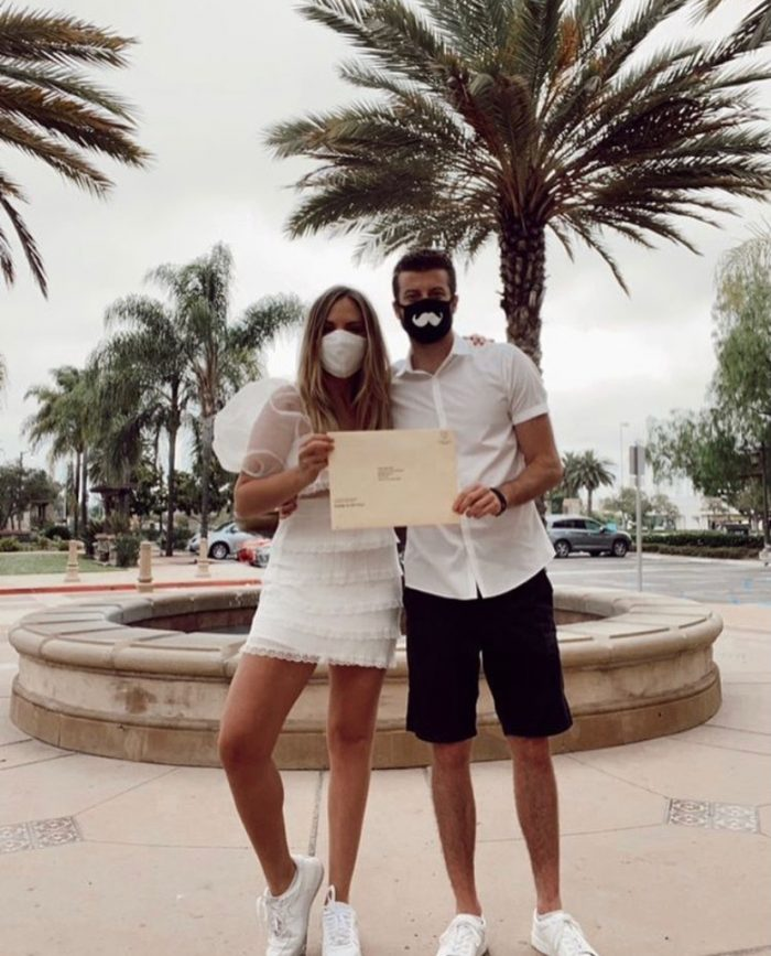 Singer Michelle Ray with Her Fiancé Holding Their Marriage Certificate While Wearing Masks