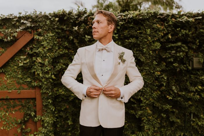 Real Groom Wearing White Suit and Bow Tie With Black Suit Pants