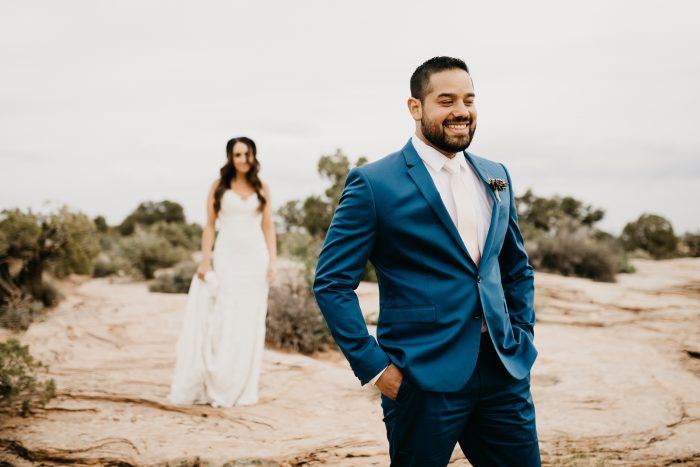 Real Bride Wearing Sottero and Midgley Wedding Dress Standing Behind Real Groom Wearing Navy Blue Suit