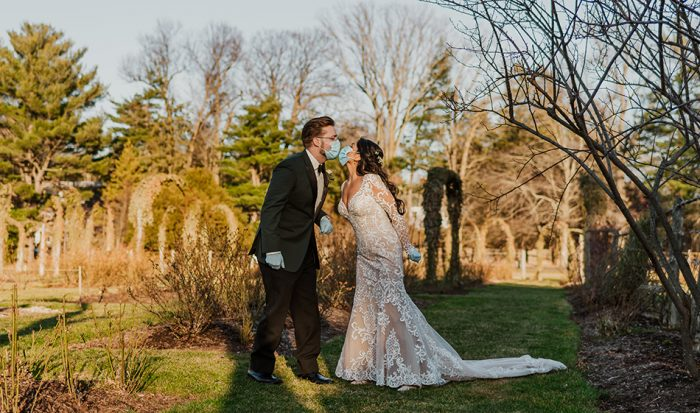 Groom with Real Bride Kissing Through Masks and Wearing Sottero and Midgley Wedding Dress Dakota