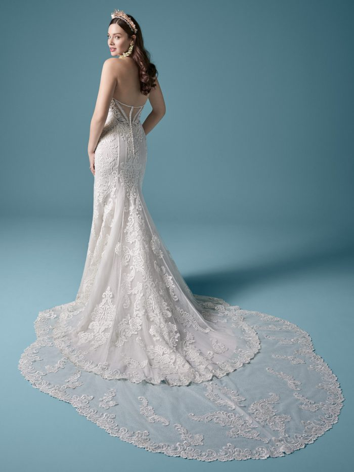 Model Wearing Long Train Elegant Lace Sheath Wedding Gown Called Erin Marie by Maggie Sottero