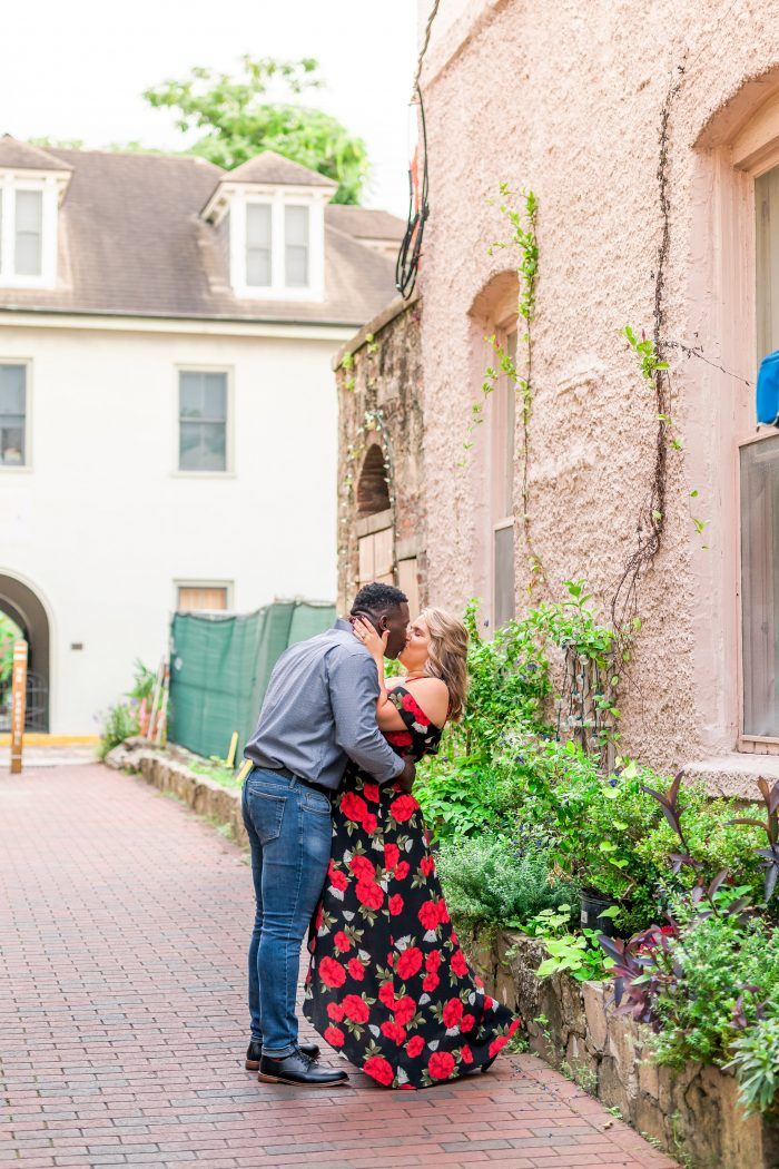 Curvy Bride with African American Groom Kissing While Taking Engagement Photos