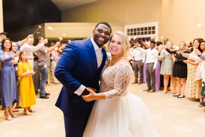 African American Groom Smiling and Holding Hands with Real Bride During Florida Wedding Reception