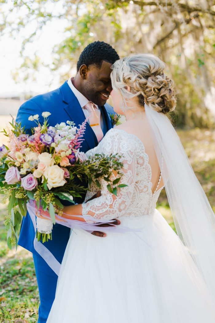 Groom Smiling at Curvy Bride Wearing Plus Size Lace Ball Gown Wedding Dress Called Mallory Dawn by Maggie Sottero