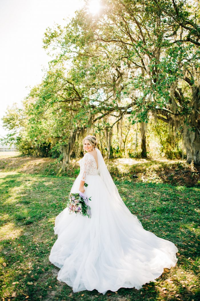 Real Curvy Bride Holding Colorful Bouquet and Wearing Illusion Lace Ball Gown Wedding Dress Called Mallory Dawn by Maggie Sottero