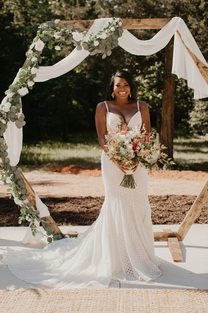 Black Bride Holding Boho Bouquet and Wearing Textured Geometric Lace Wedding Dress Called Lilana by Maggie Sottero