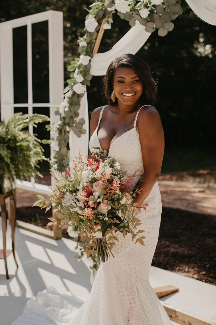 Black Bride Wearing Geometric Lace Wedding Dress Called Lilana by Maggie Sottero in Front of Flower Archway