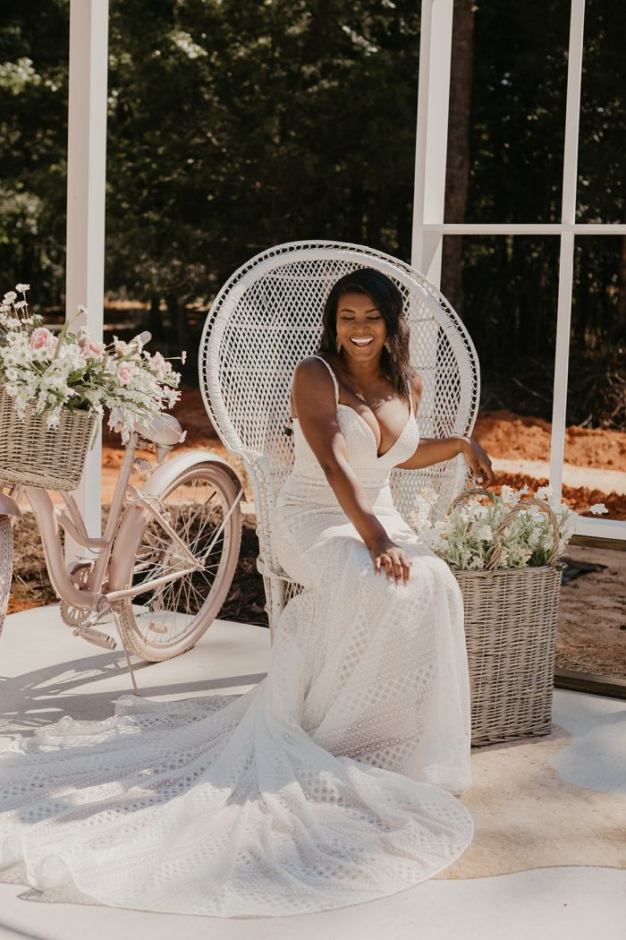 Real Bride Wearing Geometric Lace Wedding Dress Called Lilana by Maggie Sottero and Sitting on a Festival Wicker Chair