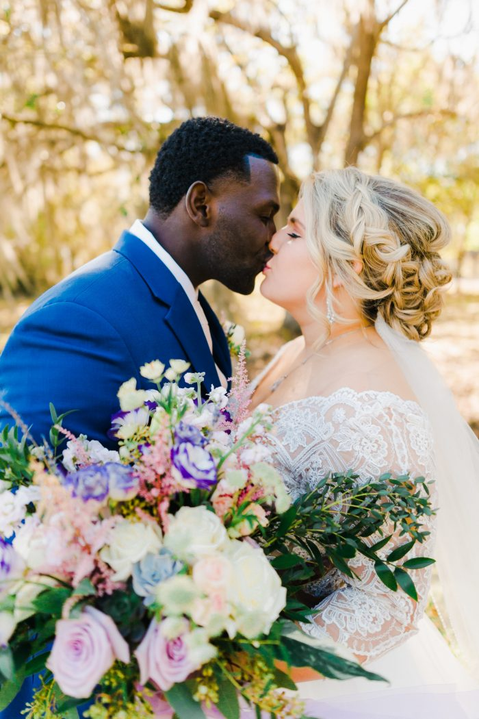 Groom Kissing Real Bride with Pastel Bouquet and Wearing Lace Bridal Gown Called Mallory Dawn by Maggie Sottero