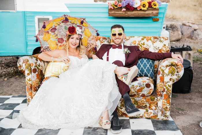 Groom on Vintage Couch in front of Colorful Trailer with Real Bride Wearing Festival Wedding Dress