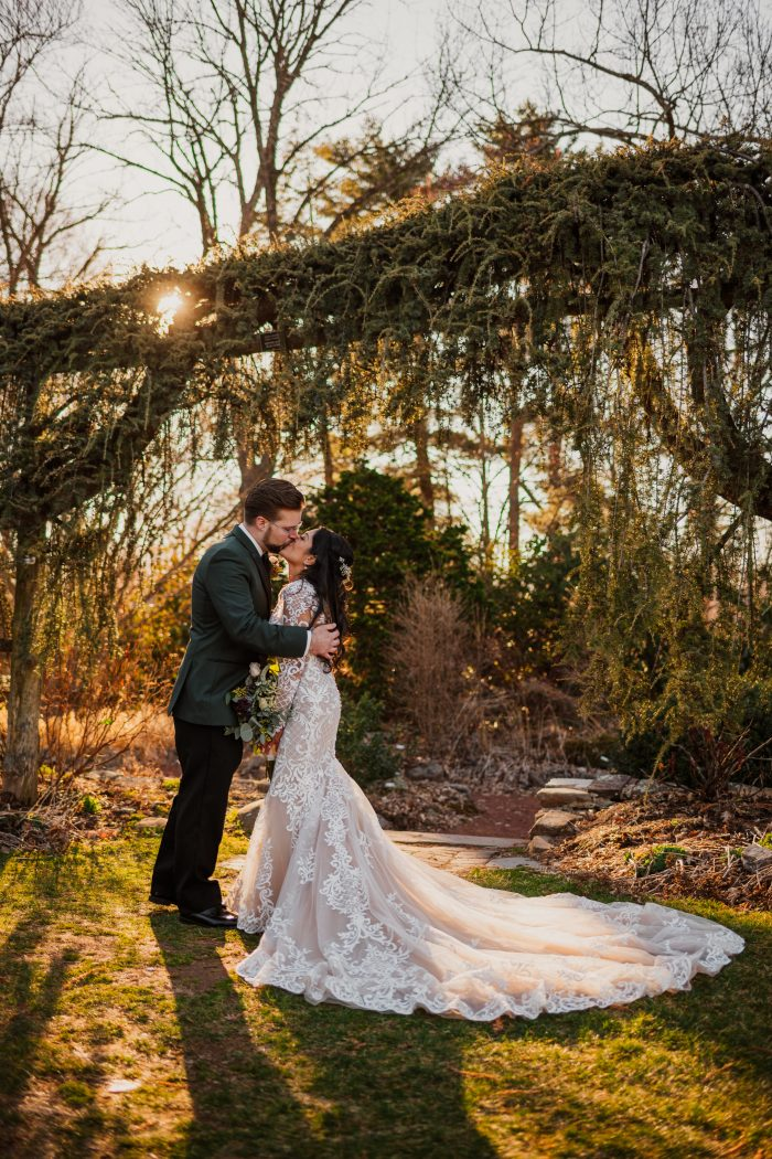 Groom Kissing Real Bride Wearing Illusion Lace Sleeve Wedding Dress Called Dakota by Sottero and Midgley