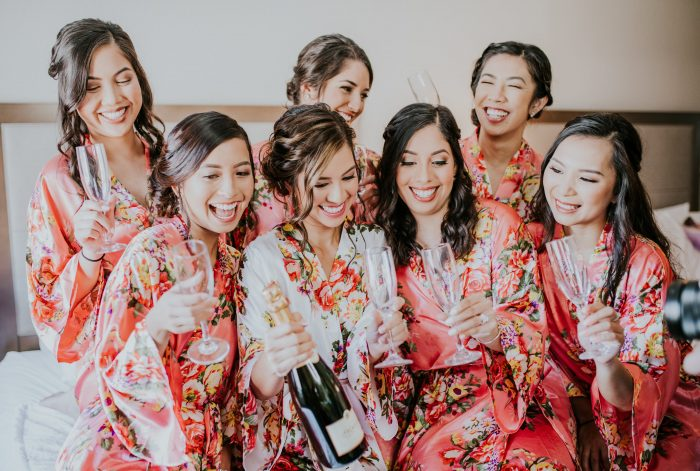 Real Bride with Bridesmaids Popping Open a Bottle of Champagne on Her Wedding Day