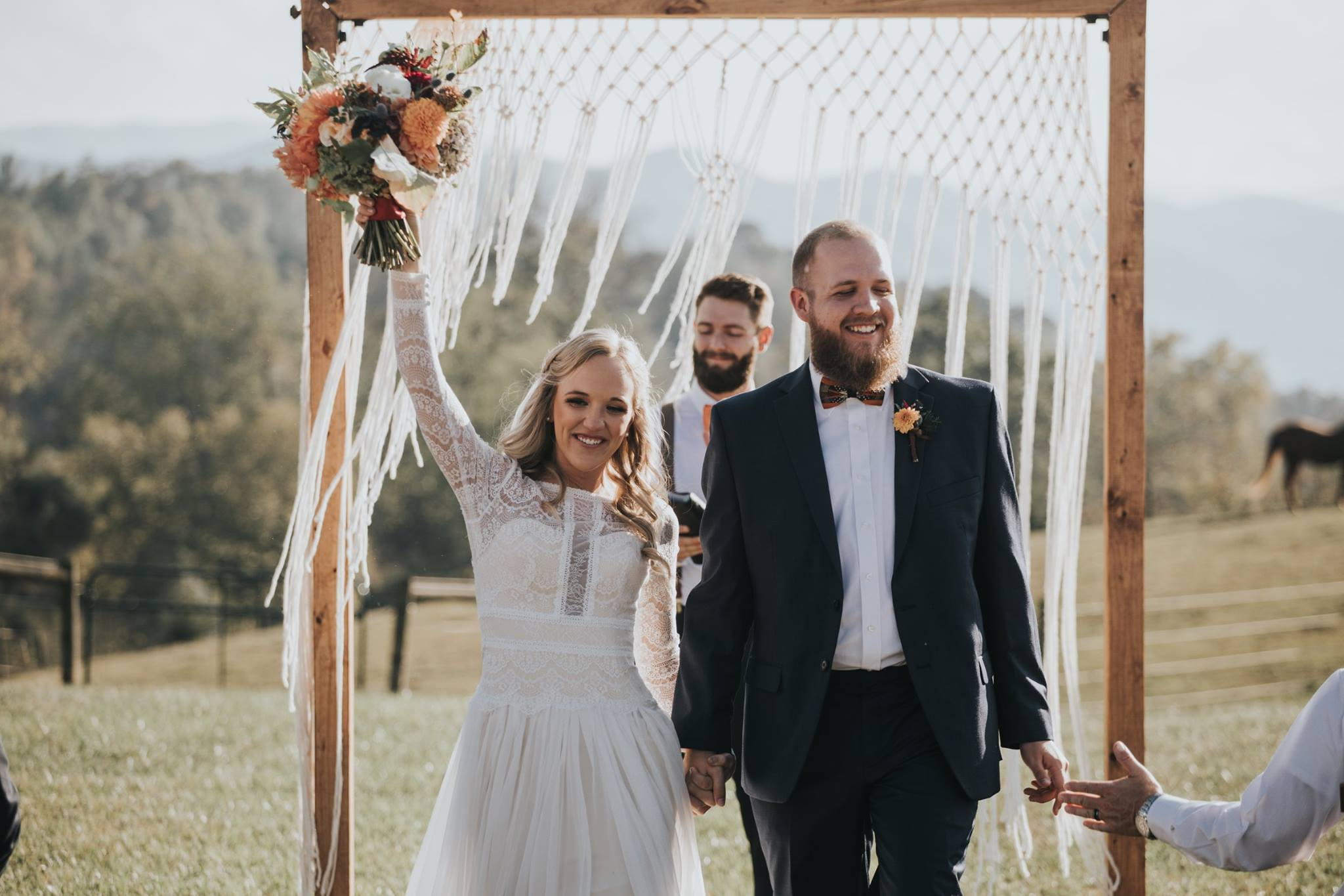 Groom with Real Bride at Boho Festival Wedding Walking Away from Rustic Wedding Arch
