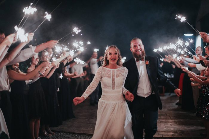 Groom with Real Bride Running Through Sparklers After Evening Reception