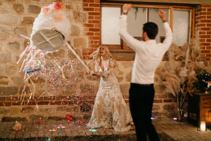 Groom with Real Bride Swinging at Pinata at Real Festival Wedding