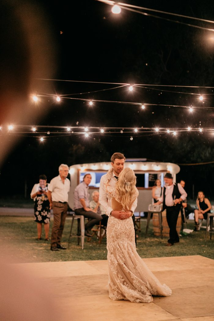 Groom Dancing Under Fairy Lights with Real Bride Wearing Lace Wedding Dress Dakota by Sottero and Midgley