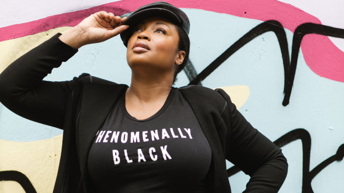"Plus Size Black Model Posing While Wearing Black T-shirt That Says ""Phenomenally Black"" Against Colored BackDrop"