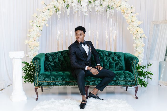 Black Groom Sitting on Luxurious Green Couch at Wedding Reception