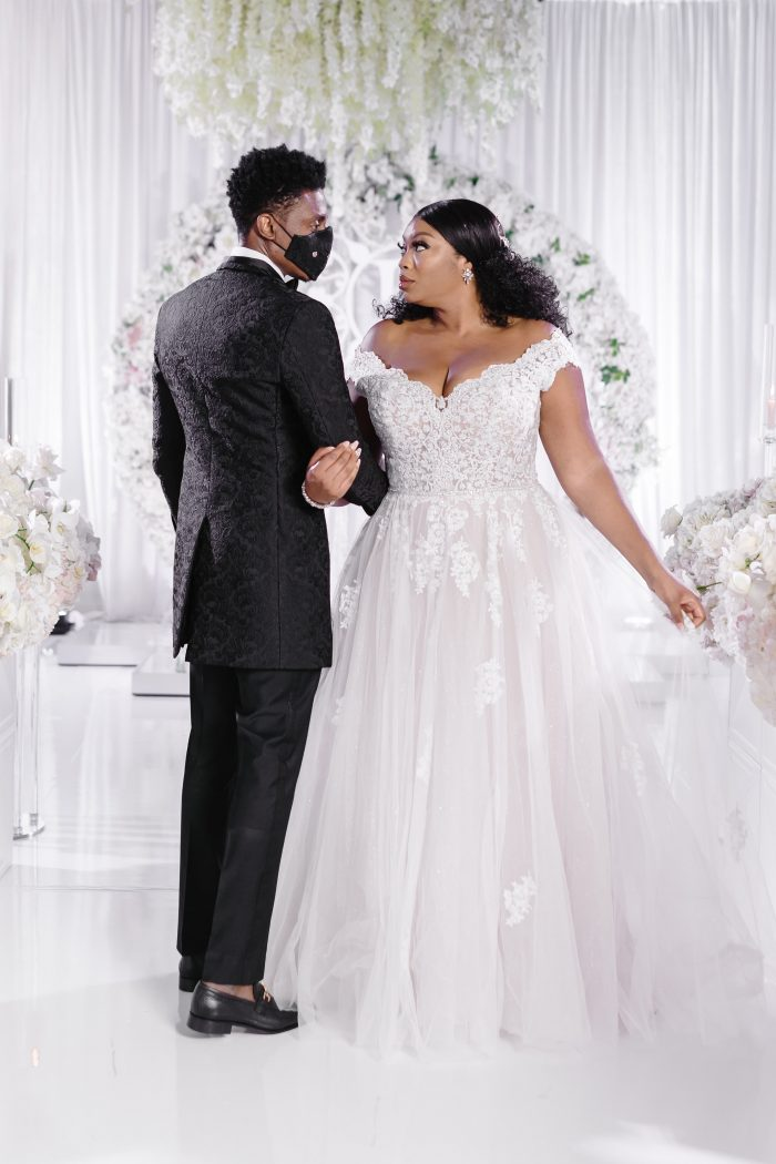 Groom Wearing a Mask with Curvy Bride Wearing Plus Size Princess Wedding Dress Called Natalie by Maggie Sottero