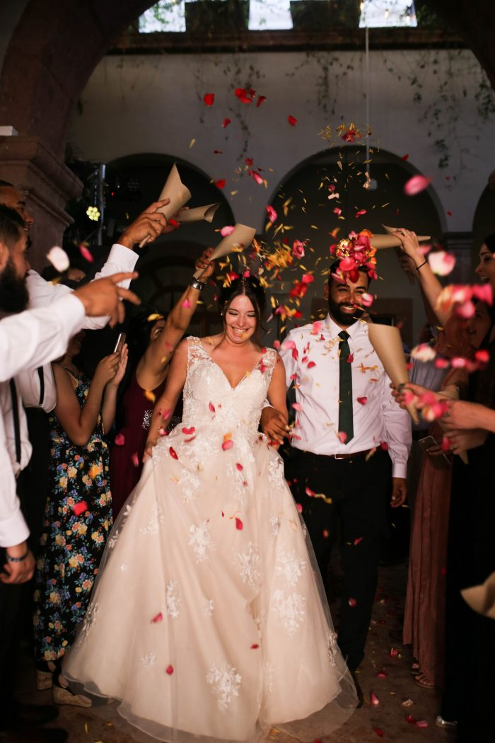 Bride and Groom Walking Through Rose Petals Confetti During Wedding Recessional