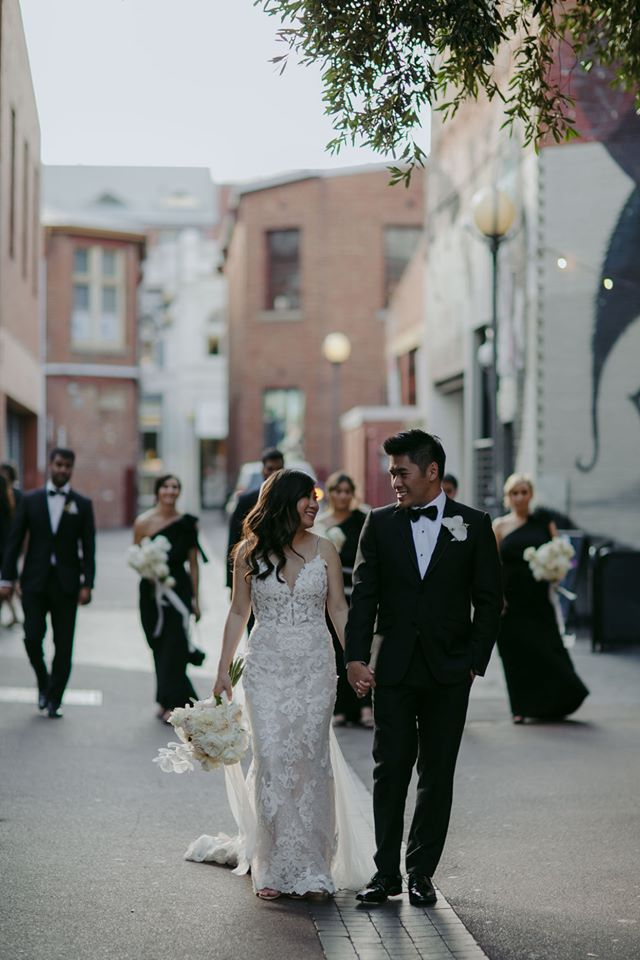 Groom Walking with Real Bride Wearing Tuscany Lace Wedding Dress During Multicultural Wedding