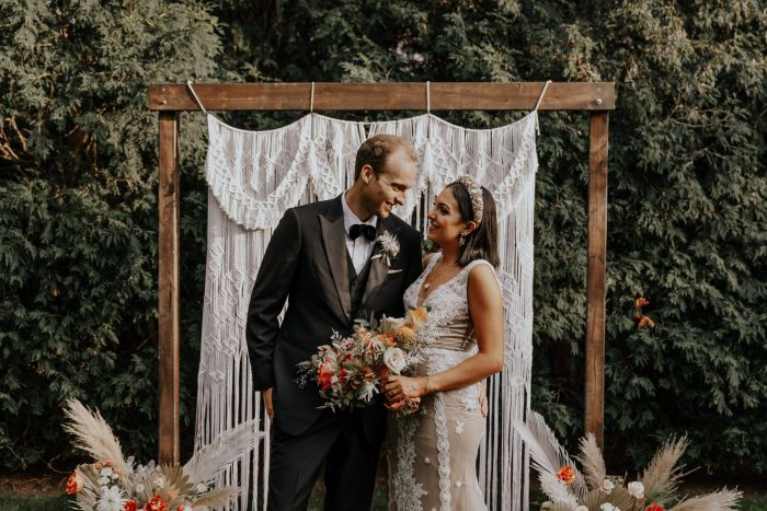Groom with Real Bride Under Arbor for Backyard Elopement Ceremony