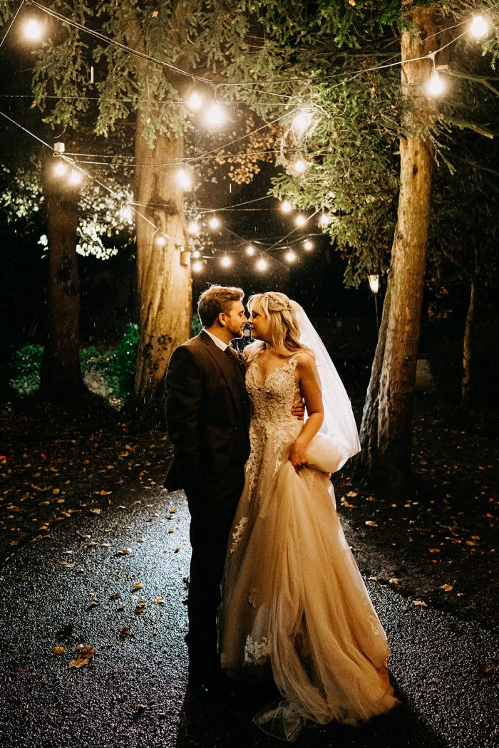 Groom Under Fairylights with Bride Wearing Boho A-line Wedding Dress Called Camille by Rebecca Ingram