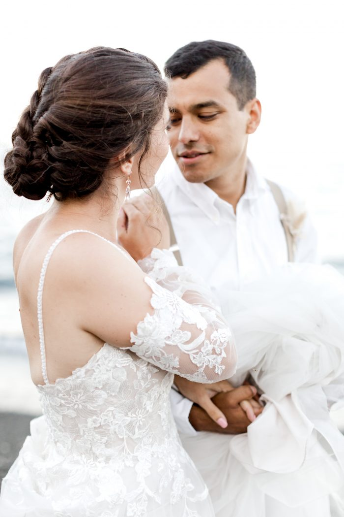 Bride Wearing Boho Wedding Dress with Detachable Sleeves and Whispering to Groom at Beach Elopement