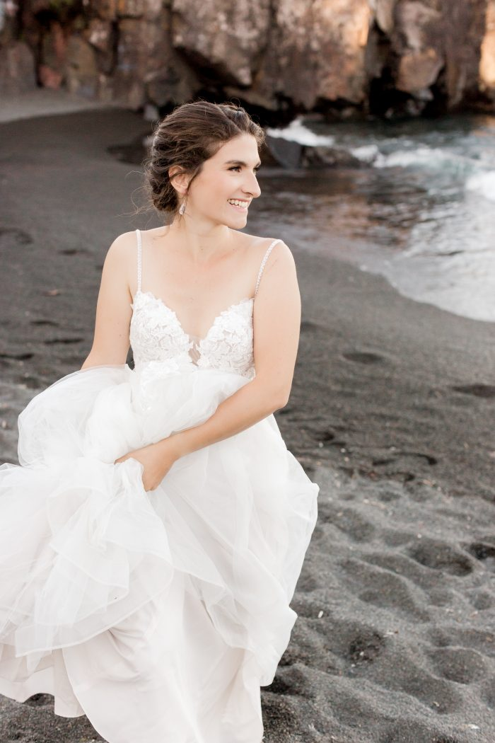 Bride Holding Maggie Sottero Wedding Dress Up as She Walks Along Black Sand Beach