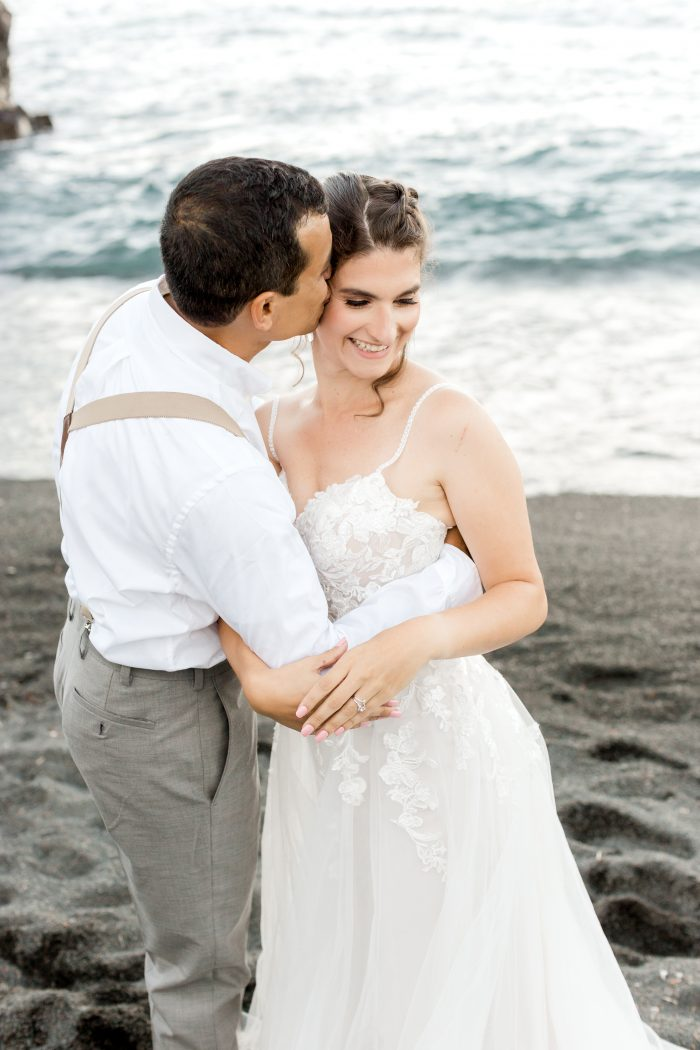 Groom on Beach Hugging Bride Wearing Boho Wedding Dress Called Stevie by Maggie Sottero