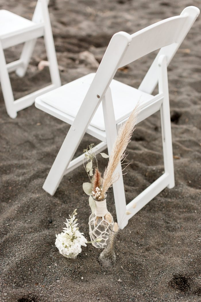 Flowers Next to White Chair on Black Sand Beach at Beach Elopement Ceremony