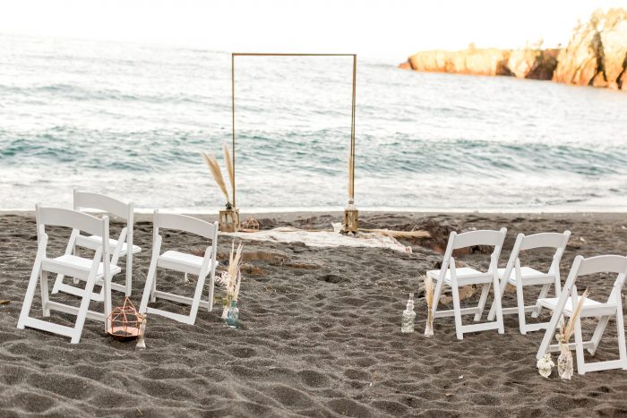 Wedding Arch Surrounded by White Chairs on Black Sand Beach or Beach Elopement