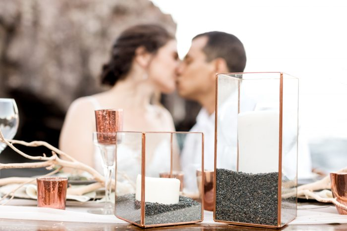 Bride and Groom Kissing Behind Sweetheart Table Featuring Little Wedding Details for Beach Elopement